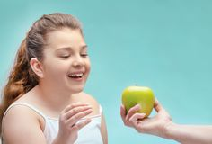 Mom holds out a green Apple to a fat kid . new life, diet, proper nutrition for children ,parental control of nutrition. problem royalty free stock image