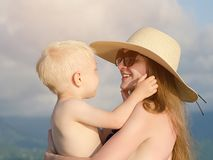Mom holds a small son in her arms and smiles. Beach, hat, sunny day.  Royalty Free Stock Photography