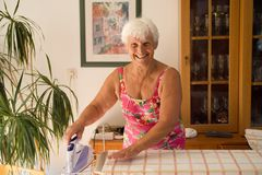 Mom at home ironing with a steam iron - homemaker Royalty Free Stock Images