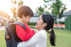 Mom hug and carry her son. Preparing to send her children back to school in morning. Mother playing with kids. Education and Back royalty free stock photos