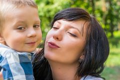 Mom hug and kiss their small son. Happy family - Mom and child-. For a walk in the park. Family resting in the park in sunny day stock photography