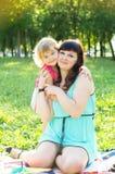 Mom hugging daughter outdoors Stock Photos