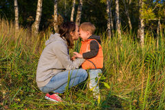 Mom hugging her son, soothe a crying baby. Small boy crying in the arms of her mother. The grass at the edge of an autumn forest Stock Photo