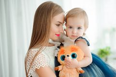 Mom hugging and kissing his little daughter stock photos