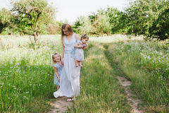 Mom hugging two daughters outdoors Stock Photos