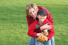 Mom Hugging Young Sports Son. Mom hugging young son after a baseball game, outdoors, against background of green grass. Horizontal format Stock Photo