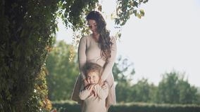 Mom hugs baby daughter outdoors stock video