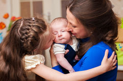 Mom hugs baby and older daughter Royalty Free Stock Images