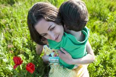 Mom hugs the boy. Mother hugs the boy. A women is walking with her son across the field. The kid is sitting at mother`s arms and hugs her. Mom`s embrace royalty free stock photo