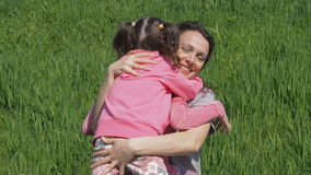 Mom hugs children in nature. Woman with little girls in a park on green grass. Family hugging on lawn. stock video