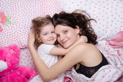 Mom hugs her daughter lying in bed Royalty Free Stock Image