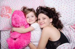 Mom hugs her daughter lying in bed Stock Photos