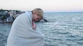 Mom hugs her son on the beach and wraps his blanket that would warm. He strokes the boy`s face with his hand. They smile stock video