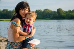 Mom hugs his son, laughs and holds a paper airplane near a river at sunset. In summer royalty free stock images