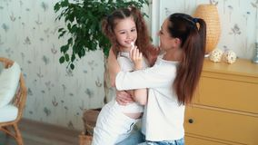 Mom hugs and kisses cute daughter, they laugh and have fun time, slow motion. Concept happy family stock footage