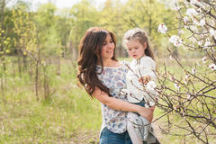 Mom hugs kisses daughter in the lush spring garden Stock Images