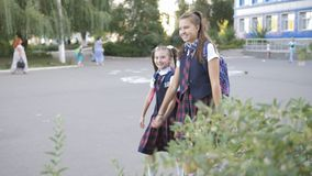 A happy mother meets her two daughters from school. Mom hugs and kisses her children in school uniform. stock video