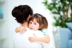 Mom hugs little daughter. Maternal love and family happiness. Happy children and parenthood.  stock photo