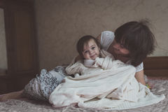 Mom hugs and plays with her daughter hide and seek on  bed, life Stock Images