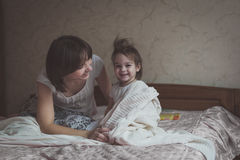 Mom hugs and plays with her daughter hide and seek on  bed, life Stock Image