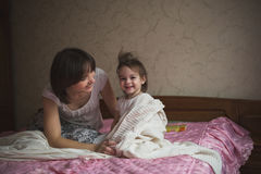 Mom hugs and plays with her daughter hide and seek on  bed, life Royalty Free Stock Photography