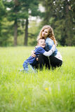 Mom hugs son. Young mother plays with her son in a meadow royalty free stock image