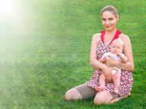Mom with an infant on a green lawn royalty free stock photo
