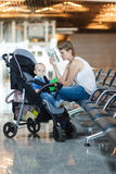 Mom and infant waiting for his flight at the airport Royalty Free Stock Image