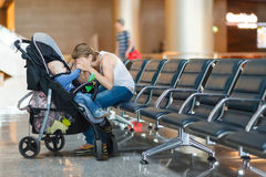 Mom and infant waiting for his flight at the airport Royalty Free Stock Photos