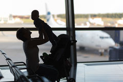 Mom and infant waiting for his flight at the airport Royalty Free Stock Images