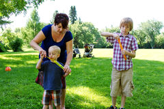 Mom instructing young son how to blow bubbles. Mom instructing son on blowing bubbles at park Royalty Free Stock Photography