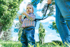 Mom insures her child during a walk. Mothers teach to walk on the road Royalty Free Stock Image