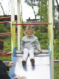 Mom insures her daughter when she comes down from the children slide stock images