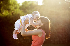 Mom keeps daughter in her arms stock images