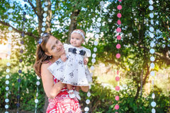 Mom keeps daughter in her arms in a beautiful dress Royalty Free Stock Photo