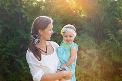 Mom keeps daughter in her arms and plays on the nature Royalty Free Stock Images