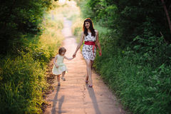 Mom keeps daughter's hand and walks the walk on the nature in sunset light Stock Photography