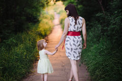 Mom keeps daughter's hand and walks the walk on the nature in sunset light Stock Photo