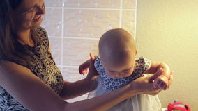 Mom keeps a little baby girl in a dress in her hands.  stock video