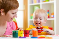 Mom and kid boy paint together at home Stock Photos