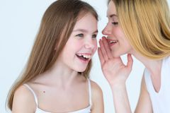 Mom kid communication mother sharing secret. Mom and kid communication. mother sharing a secret. women whispering something into her daughter ear Stock Images