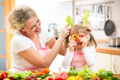 Mom and kid cooking and having fun in kitchen Stock Image
