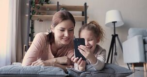 Mom and kid daughter having fun video calling on smartphone
