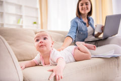 Mom and kid. Focus on baby girl lying on the couch while her mom is sitting near with laptop Royalty Free Stock Images