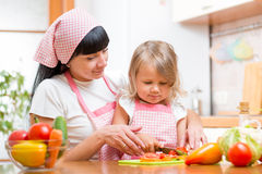 Mom and kid girl cooking and cutting vegetables on kitchen Royalty Free Stock Photography