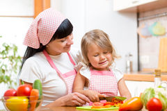 Mom and kid girl cutting tomatoes on kitchen Royalty Free Stock Photography