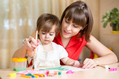 Mom and kid girl paint together at home Royalty Free Stock Photos