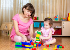 Mom and kid girl play block toys at home. Mom and kid girl playing block toys at home Stock Photos