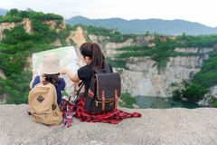 Mom and kid holding maps and travel backpacks sitting victorious facing on the outdoors grand canyon for education nature. Travel Concept royalty free stock photo