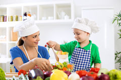 Mom with kid making lettuce. At kitchen Royalty Free Stock Image